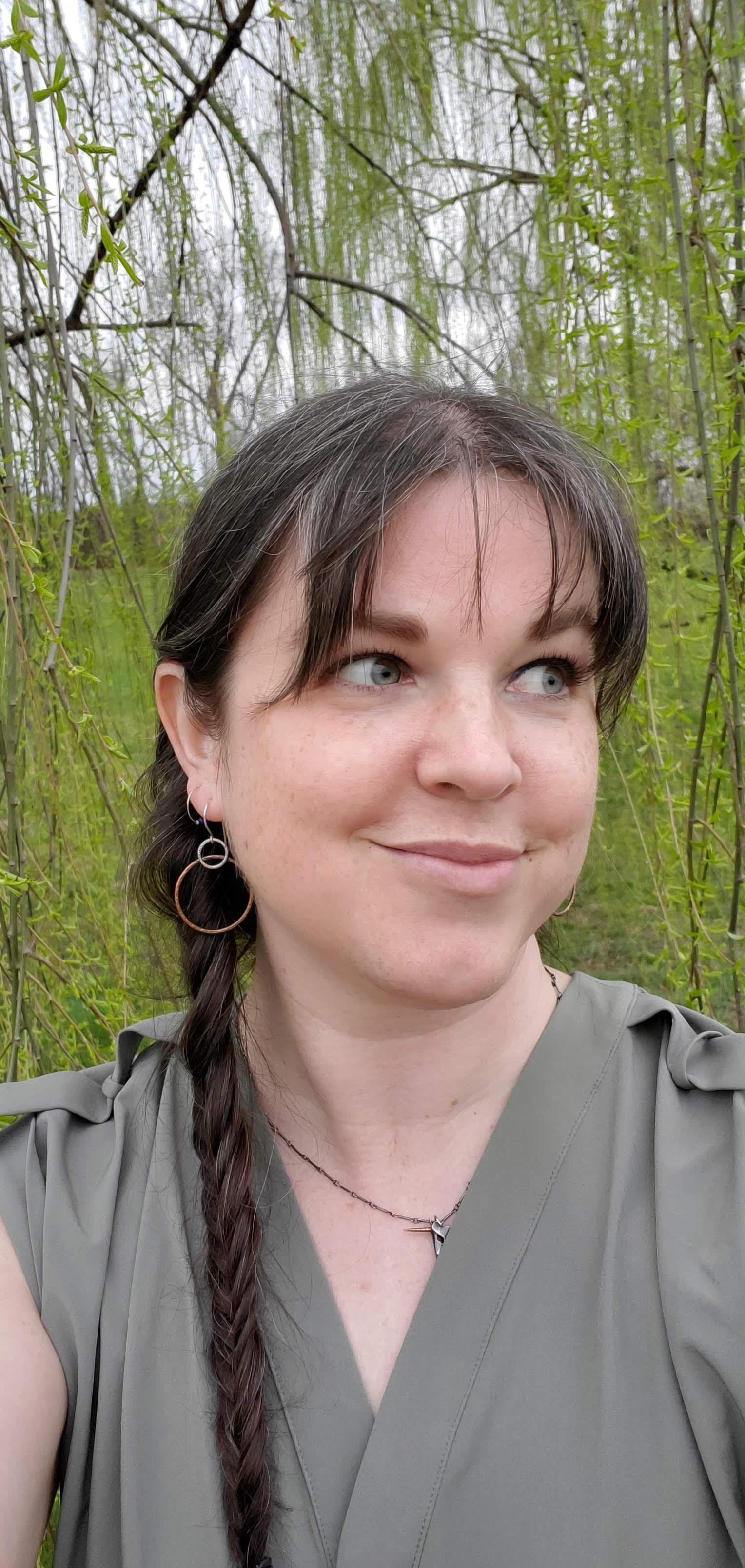 Author Elizabeth with braided brown hair and green shirt.